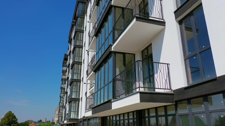 Beautiful design of multistorey building. New apartment with balconies against blue sky. Exterior of residential building. Camera rising up. Slow motion. Royalty-Free Stock Footage #1058218567