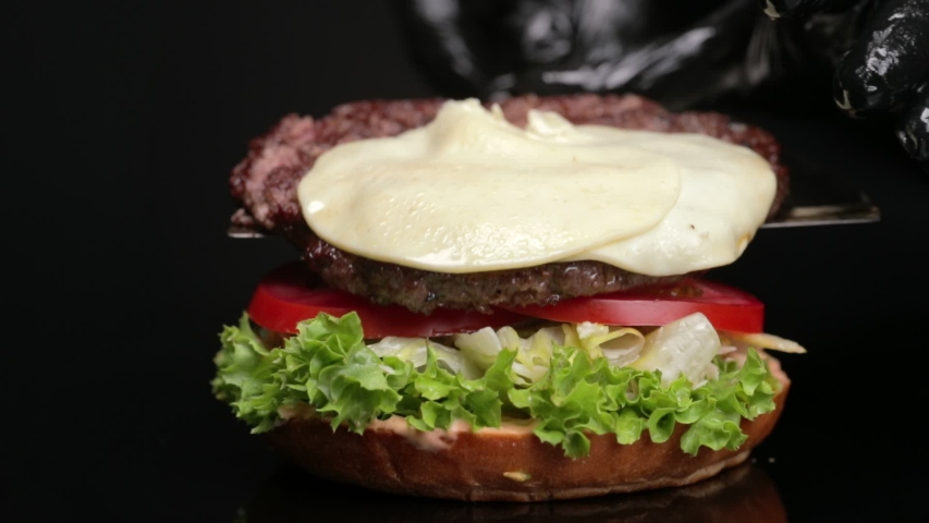Chef making burger. Slow motion Close-up shot of chef's hands preparing a delicious hamburger with beef cutlet and cheese.  Isolated on black background and reflection of  black table. Camera zoom-in. | Shutterstock HD Video #1058222935