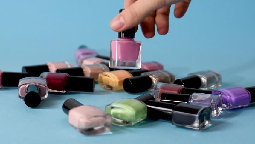 Female take pink nail polish. Nail varnish set, woman take pink nail polish bottle. Royalty-Free Stock Footage #1058223850