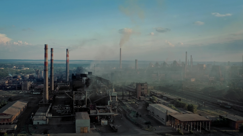 Drone shot of industrial zone with thick smog and burning fossil fuels. Factory zone pan shot left to right of polluted city, many factory chimneys in city area Royalty-Free Stock Footage #1058227714