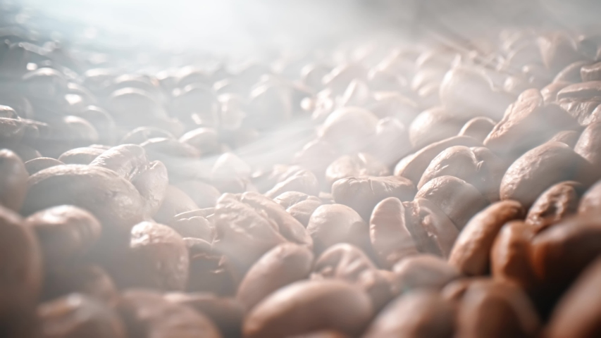 Close up of seeds of coffee. Fragrant coffee beans are roasted smoke comes from coffee beans. | Shutterstock HD Video #1058228644