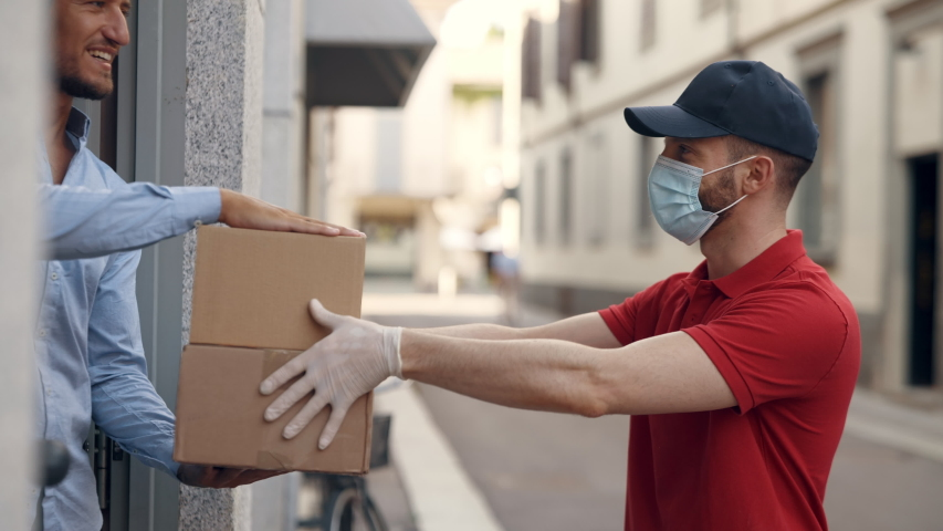 An young mailman courier with a protective mask and gloves is delivering a parcel directly to a customer home with safety. Concept of courier, home delivery, e-commerce shipping, virus, covid Royalty-Free Stock Footage #1058229220