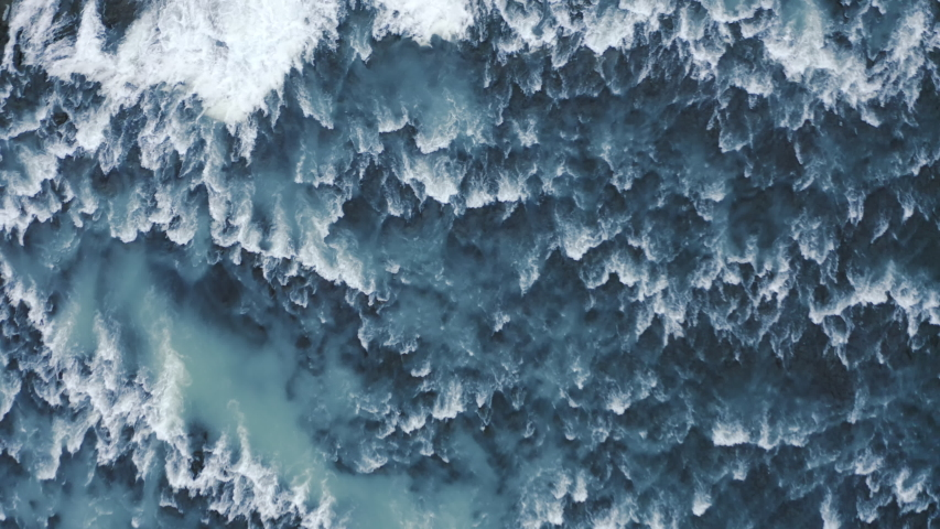 Aerial drone top down view at strong streams of cold blue water from waterfall at Iceland, 4k Beautiful pattern od ice, water and foam.