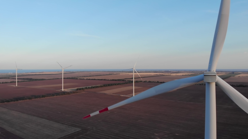 Aerial of wind turbines energy production 4k shot on sunset near Black Sea. Windmills generating clean renewable energy for sustainable development | Shutterstock HD Video #1058230000