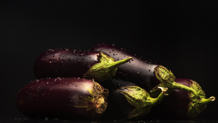 Eggplants spinning around their axis on black background. Eggplant with water droplets. Vegetables. | Shutterstock HD Video #1058233234