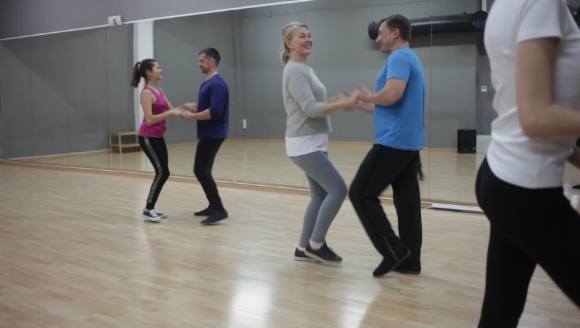Cheerful adults learning to dance kizomba with partners in dancing group class