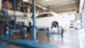 Blurred Background of Technicians Car Repair Center with Mechanics and Electric Lift for Cars in Service Station. Electric Lift Is Lifting the Car Up and Worker Removing Tire. Defocused Video