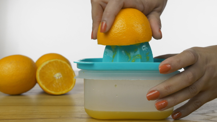 Closeup shot of woman hands squeezing out fresh orange juice on a manual juicer. Hands of an Indian female juicing orange fruit on a manual plastic squeezer against the white background