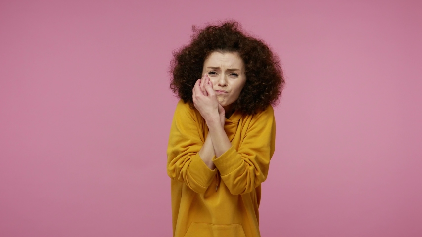 Dental problems. Unhealthy young woman afro hairstyle in hoodie touching sore cheek, suffering terrible toothache, horrible pain from cavities and gum disease. indoor   isolated on pink background | Shutterstock HD Video #1058243959
