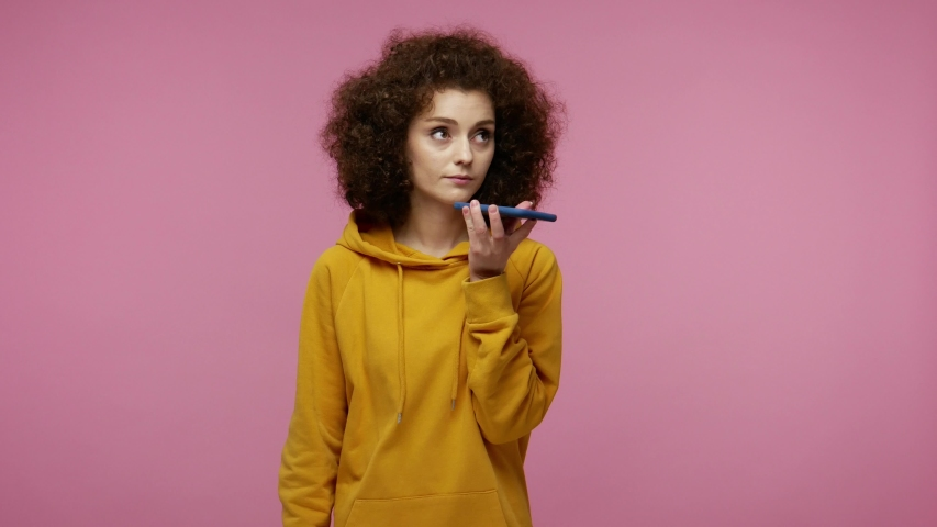 Mobile smart digital voice technology. Beautiful young woman afro hairstyle in hoodie talking to smartphone using virtual assistant, recording message or online order.   isolated on pink background | Shutterstock HD Video #1058243962