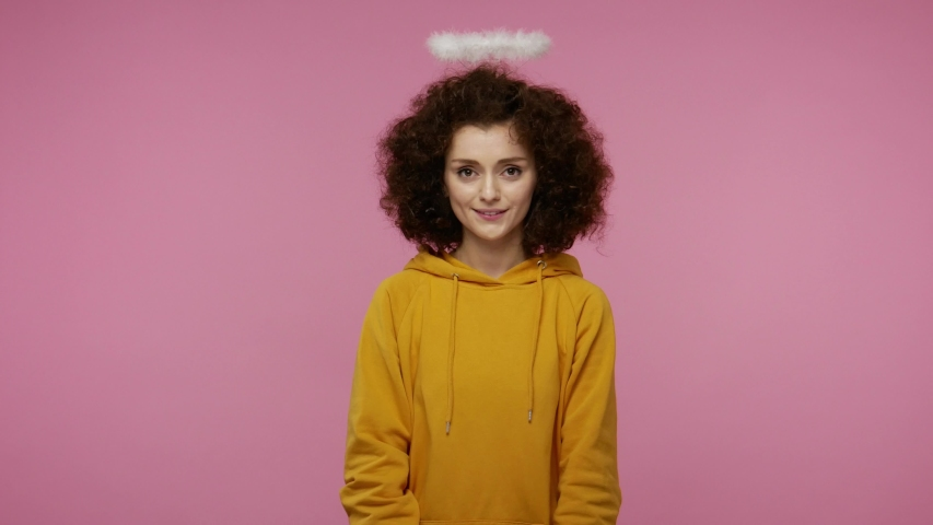 Take this present! Charming angelic young woman afro hairstyle with saint halo giving wrapped gift box to camera and smiling, congratulating on holidays, donation charity concept. studio shot isolated | Shutterstock HD Video #1058243977