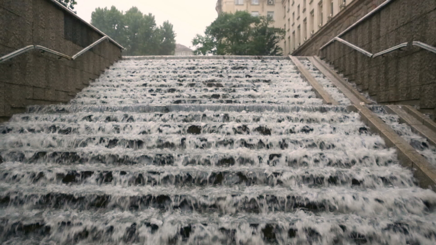 Heavy rain droplets are seen falling on concrete stairs on an underpass.