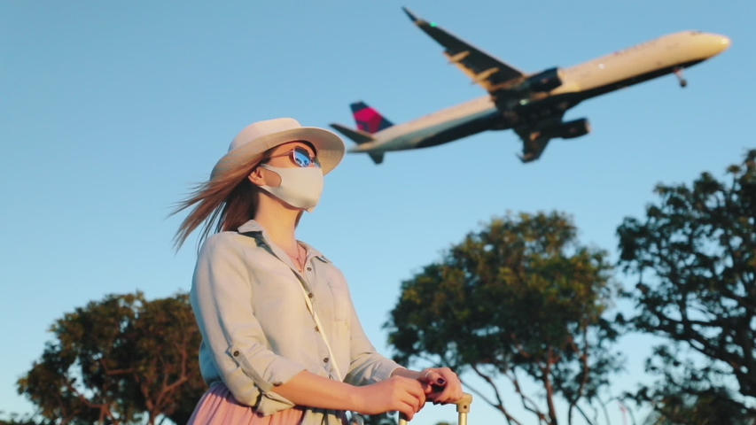 Slow motion woman in face mask is enjoying the sunset with landing airplane on background. Safe travels under COVID-19. Aircraft is arriving at the airport during coronavirus pandemic on sunny evening Royalty-Free Stock Footage #1058249143