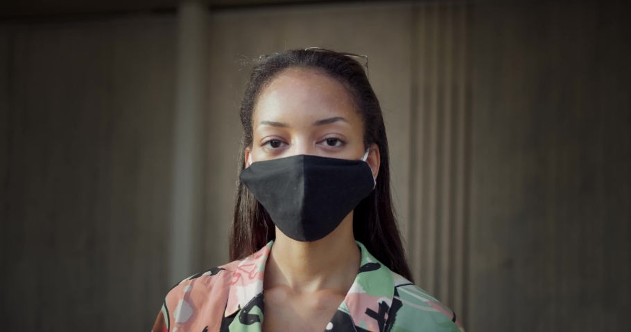 Confident portrait of mixed race young female looking serious to camera moving outdoors, close up of beautiful woman protected from virus wearing black mask at city urban street, wall on background   Shutterstock HD Video #1058251579