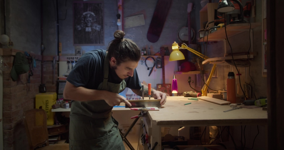 Side shot of attractive serious master guy sawing wooden plank fixed by clamp indoors, process of manual creating musical instrument guitar neck at cozy workshop with colorful background light | Shutterstock HD Video #1058251585