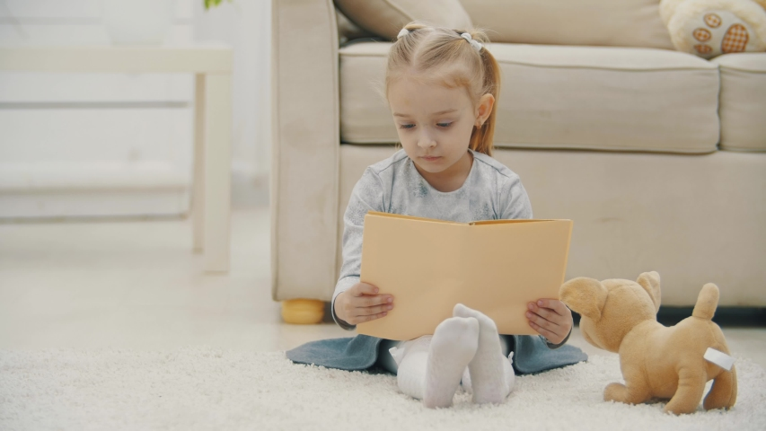 4k slowmotion video of preschool daughter holding and reading book. | Shutterstock HD Video #1058257261