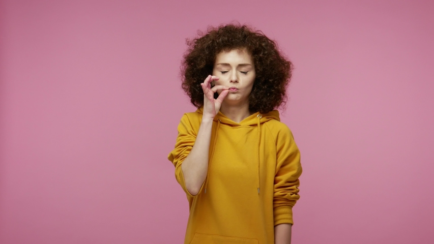 I won't tell anyone! Intimidated young woman afro hairstyle in hoodie zipping lips and looking scared, covering mouth promising to keep terrible secret. indoor studio shot isolated on pink background | Shutterstock HD Video #1058259352