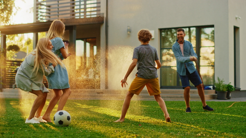 Happy Family of Four Playing with Garden Water Hose, Spraying Each Other. Mother, Father, Daughter and Son Have Fun Playing Games in the Backyard Lawn of Idyllic Suburban House on Sunny Summer Day Royalty-Free Stock Footage #1058261899