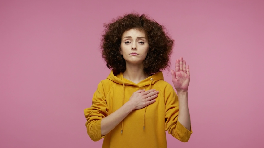 Honest responsible young woman afro hairstyle in hoodie raising hand, touching chest and taking vow, saying promise, looking at camera trustworthy reliable. indoor  isolated on pink background | Shutterstock HD Video #1058263018