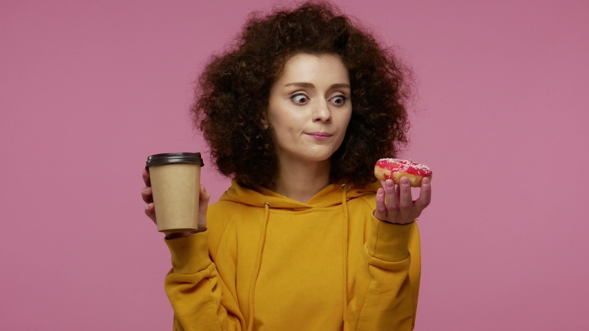Young woman afro hairstyle in hoodie drinking cup of coffee and looking with great desire at donut, craving to bite sweet confectionery, sugar glucose and junk food concept. indoor studio   isolated | Shutterstock HD Video #1058263042