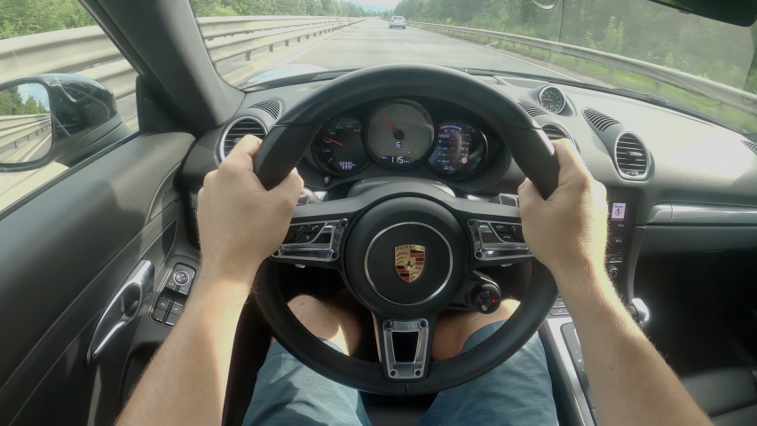 LJUBLJANA, SLOVENIA, MAY 2020, POV: Man is driving down the empty highway in a brand new black Porsche supercar. Awesome first person shot of a drive down an empty freeway in a luxury Porsche car. Royalty-Free Stock Footage #1058263195