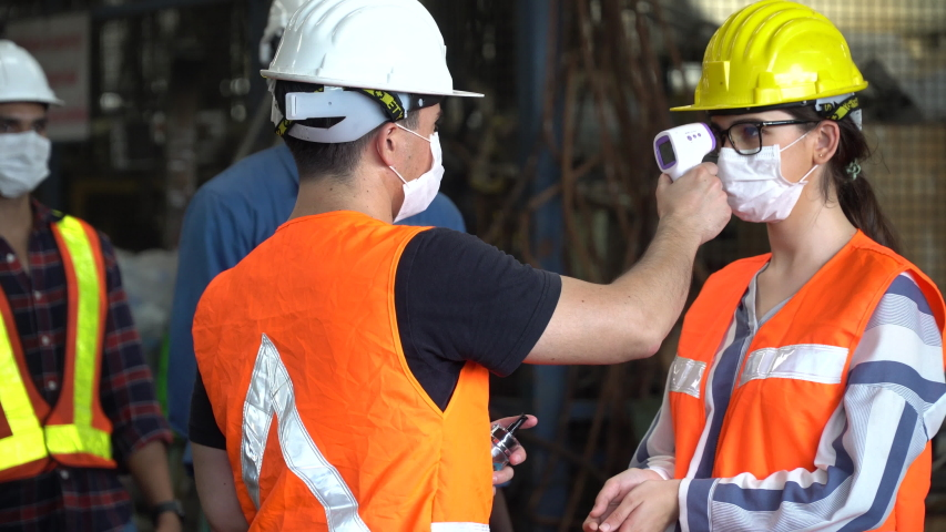 foreman wear protective face mask scanning body temperature measuring fever by thermometer and using  hand sanitizer alcohol gel to worker distancing before entering working in Industrial plant Royalty-Free Stock Footage #1058266216