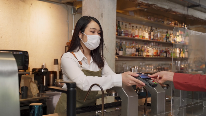 Woman customer paying touchless credit card to waitress with face mask on counter then next customer come and order food by social distancing rule for new normal lifestyle in restaurant during covid.