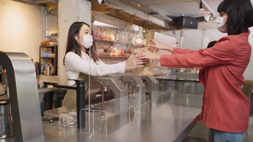 Woman customer receiving food from waitress with face mask on counter then next customer come and order food by social distancing rule for new normal lifestyle in restaurant during covid pandemic.