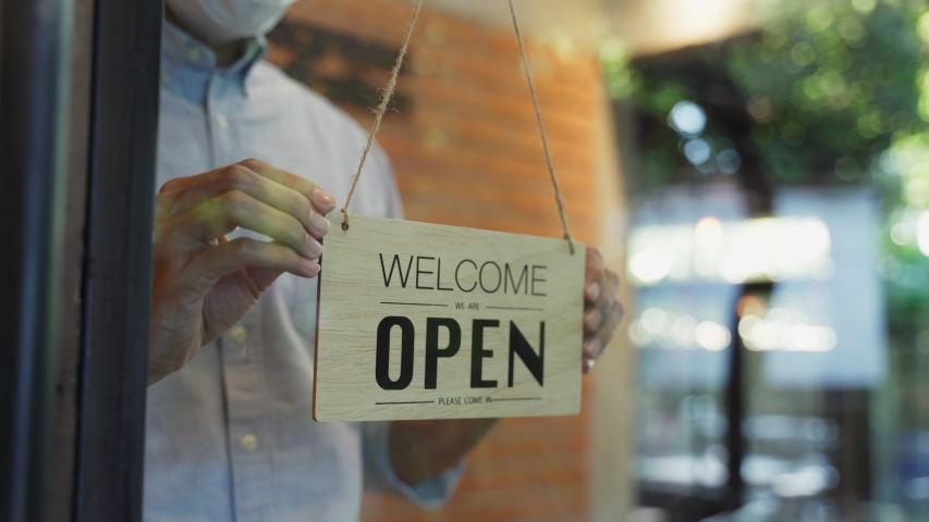 Cafe or restaurant and business reopen after Coronavirus quarantine is over. Man with face mask turning a sign from closed to open on a door shop. Small food shop business after post covid lockdown. Royalty-Free Stock Footage #1058267041