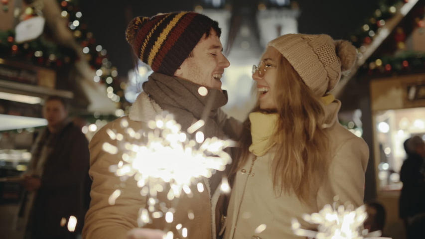 Charming couple in love kissing and burning bengal lights at festive european street fair. Lovers having fun and enjoying the moment in Prague on Christmas Eve. Concept of travelling and festivals. Royalty-Free Stock Footage #1058269054
