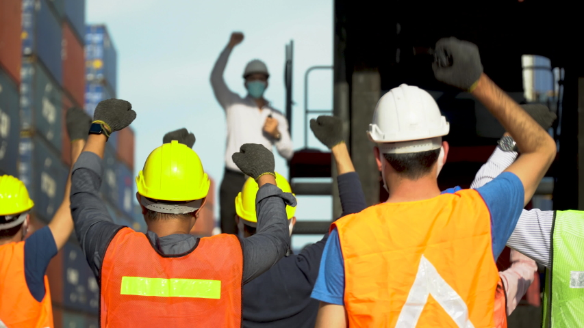Workers protest in Cargo freight ship for import export logistic During corona virus or covid 19 outbreak . Group of protestors fists raised up in the air . Strike of labor in industry  Royalty-Free Stock Footage #1058271403