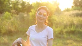 Beautiful brunette woman in 30s rides bicycle at sunset in sunny park.Close up video portrait of pretty young girl on bike smiling for camera.Footage of cute female model holding bikes handlebars