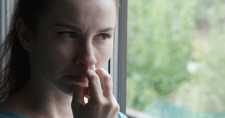 Woman with a Runny Nose Using a Nasal Spray as a Treatment Standing by the Window Royalty-Free Stock Footage #1058272789