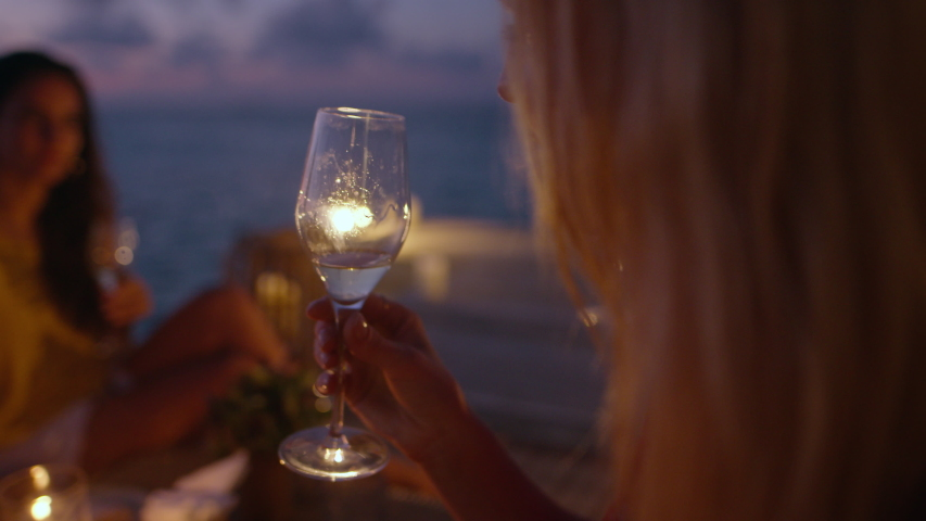 Closeup of a woman toasting wine with friends sitting at overwater villa deck in night.  Group of friends partying at luxury resort.