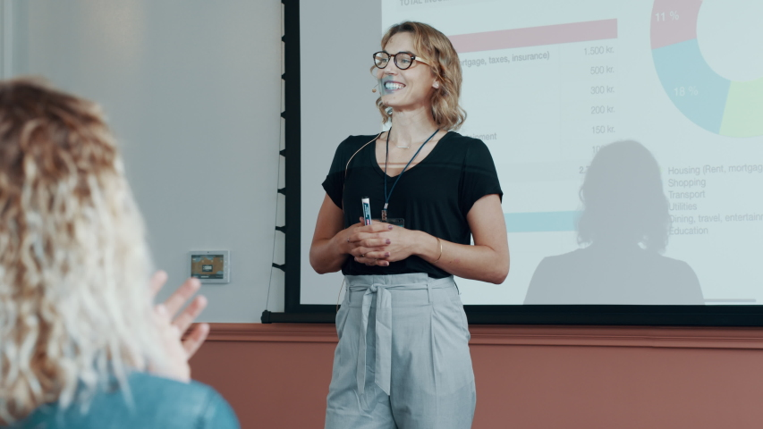 Businesswoman standing in front of a projection screen and presenting her ideas to group of people sitting in a seminar. Female professionals addressing a business conference.  Royalty-Free Stock Footage #1058273293