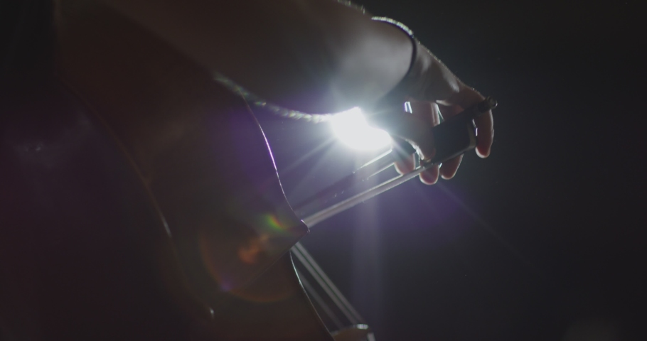 Footage of female hands playing cello violoncello . Musician Woman plays in beautiful contrabass on stage in concert . Close up . Shot on ARRI ALEXA movie camera in slow motion .