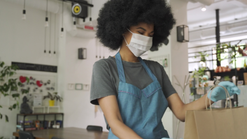 African American female cafe worker wears face mask and gloves giving takeaway food bag to customer. Mixed race waitress holding takeout order standing in coffee shop restaurant with take away client. Royalty-Free Stock Footage #1058278540