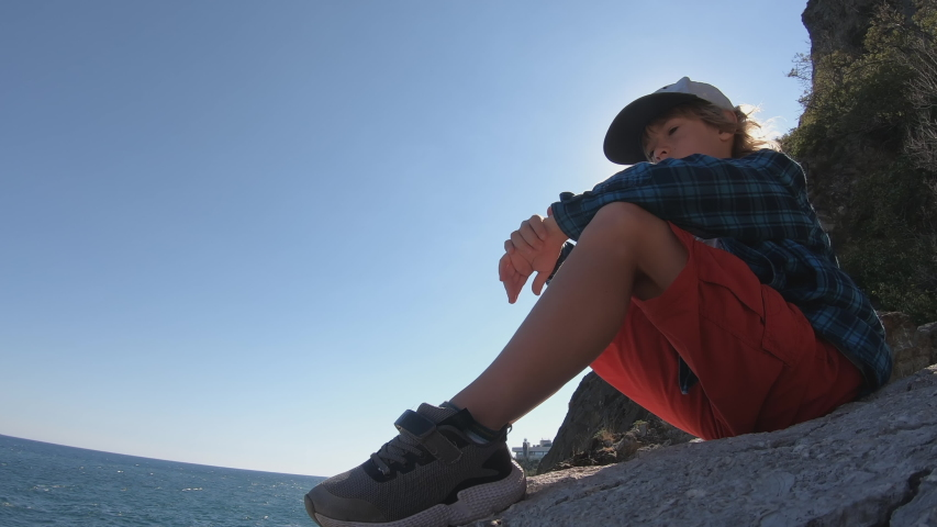 Child sitting on the top of the mountain and watching sea waves. Boy on the cliff enjoying nature landscape with blue ocean. Summer vacation, tourism, healthy lifestyle concept