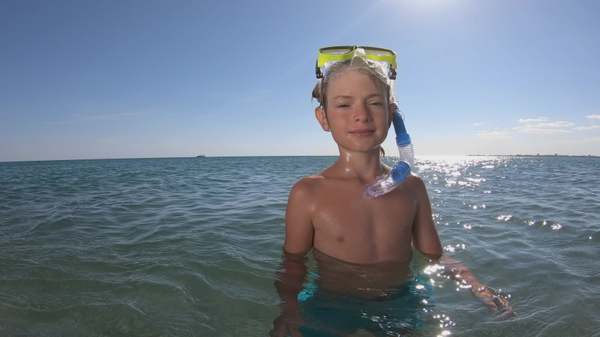 Happy child welcome you to dive in ocean with snorkel, diving mask. Snorkeling boy enjoying summer vacation snorkeling, swimming in blue sea water. Exploring underwater, resting in tropical resort.