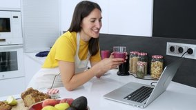 Video of beautiful young nutritionist woman having an online video call via laptop computer with a friend to showing detox handmade smoothie in the kitchen at home.