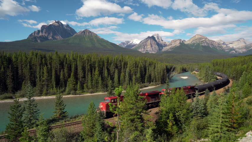 Red cargo train passing through Morant's curve in Bow Valley, Banff National Park, Alberta, Canada. Iconic landscape and railway system in the Rocky Mountains of North America. Royalty-Free Stock Footage #1058285590