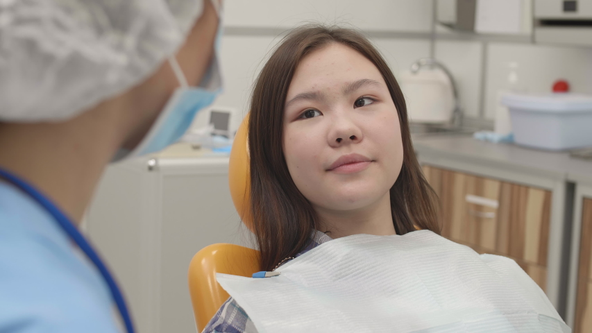 Rear view of Asian girl lying on dental chair in clinic and telling female dentist sitting in front of her about her teeth problems Royalty-Free Stock Footage #1058288494