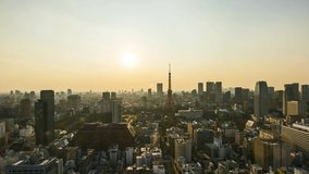 Sunrise scene at Tokyo city skyline. Cinematic look and flare effect. Tilt up. Clip may contain noise due to high ISO setting.