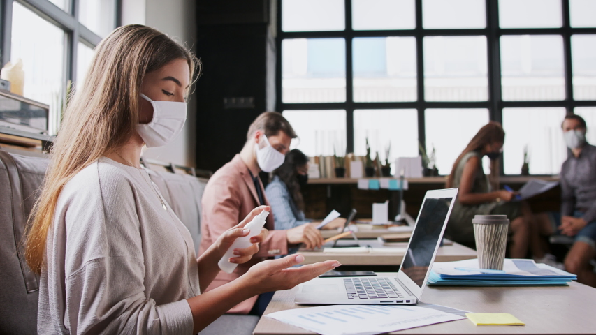 Portrait of young businesspeople with face masks working indoors in office, disinfecting laptop. Royalty-Free Stock Footage #1058307196