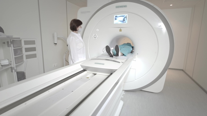 Doctor makes an MRI scan for a patient in a clinic. The girl lies in the MRI device. Magnetic resonance imaging in the study of the human body. Modern technologies in medicine. Examines lungs | Shutterstock HD Video #1058307271
