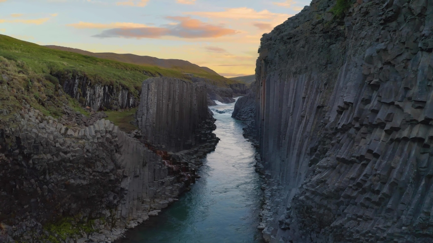 Flying through the Studlagil Canyon with the Jokulsa A Bru river in east Iceland, Europe. Filmed at sunset. 4K UHD video.