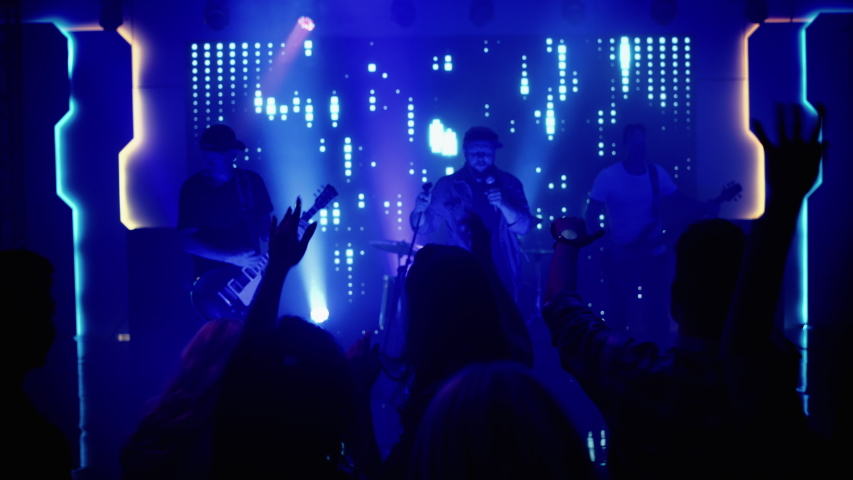 Rock Band with Guitarists and Drummer Performing at a Concert in a Night Club. Front Row Crowd is Partying. Silhouettes of Fans Raise Hands in Front of Bright Colorful Strobing Lights on Stage. | Shutterstock HD Video #1058308852