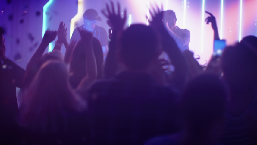 Rock Band with Guitarists and Drummer Performing at a Concert in a Night Club. Front Row Crowd is Partying. Silhouettes of Fans Raise Hands in Front of Bright Colorful Strobing Lights on Stage. | Shutterstock HD Video #1058308888
