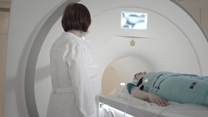 Doctor makes an MRI scan for a patient in a clinic. The girl lies in the MRI device. Magnetic resonance imaging in the study of the human body. Modern technologies in medicine. Examines lungs Royalty-Free Stock Footage #1058310088