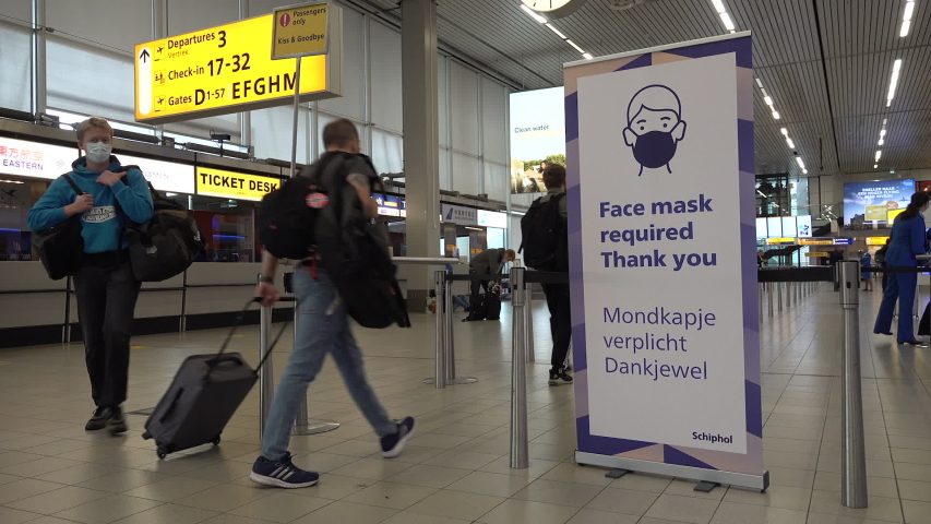 SCHIPHOL, NETHERLANDS – AUGUST 2020: Sign informs air travel passengers that face masks are required during check-in procedure at Amsterdam Schiphol Airport in the Netherlands, Covid-19 coronavirus